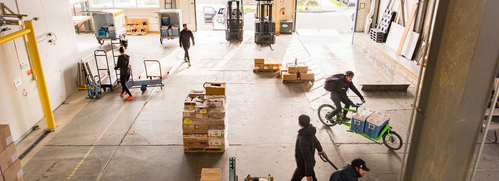 brightly lit warehouse with bikes and people walking through