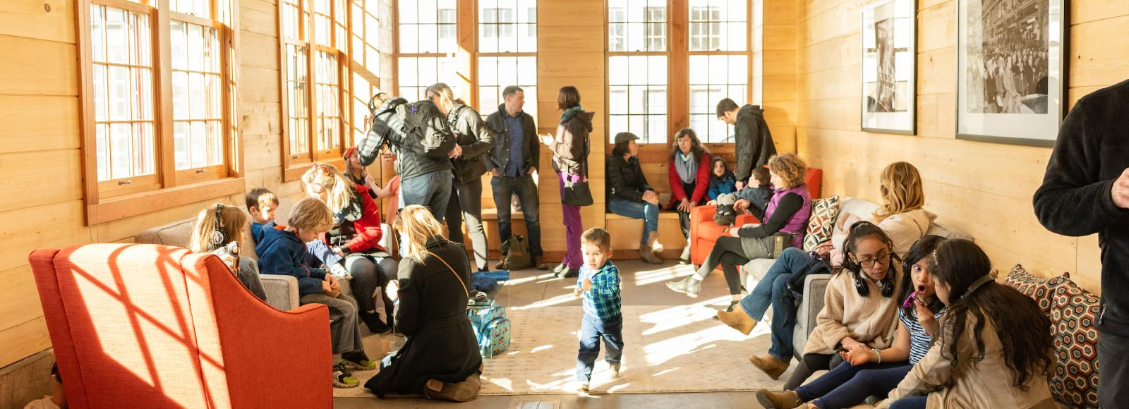 A group of parents and children enjoy a sunlit room