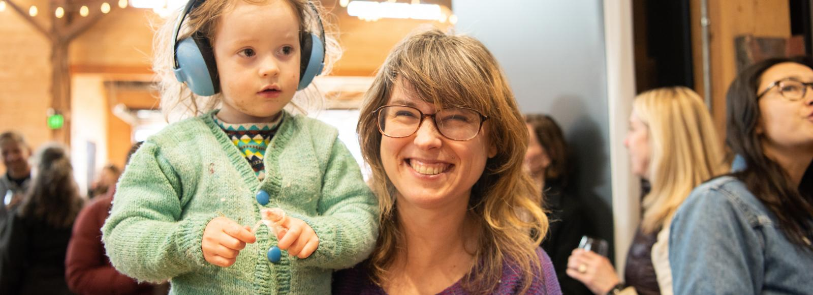 A woman in glasses and a purple shirt holds her son wearing blue headphones and a green shirt.