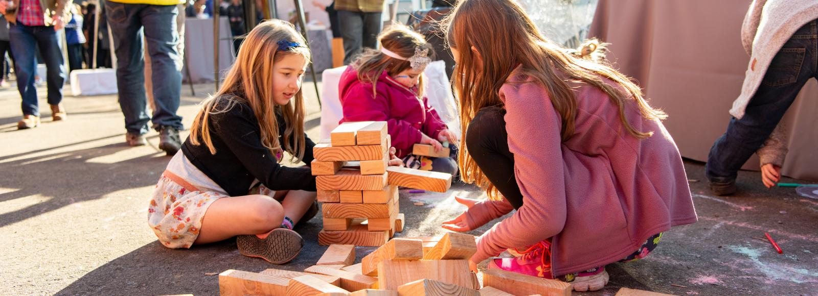 A group of kids plays with a large stacking block game outside on a sunny day.