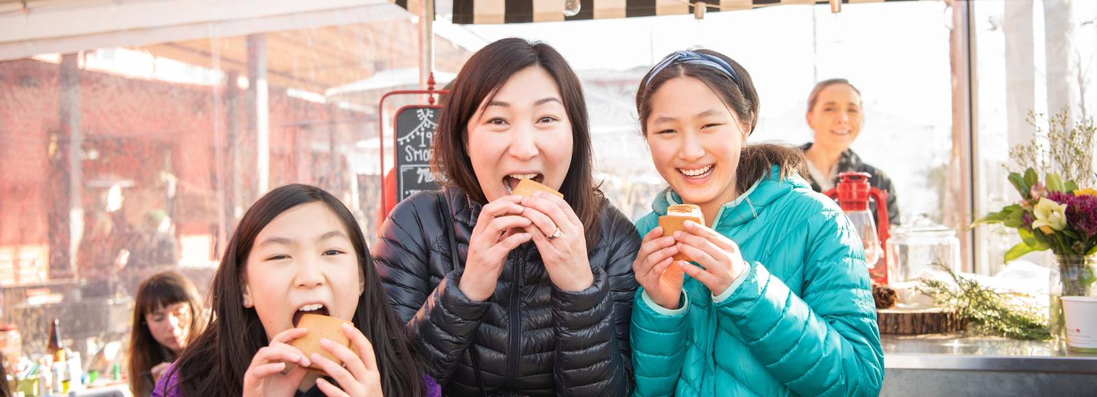 A mother and two daughters face the camera and take a bite out of s'mores.