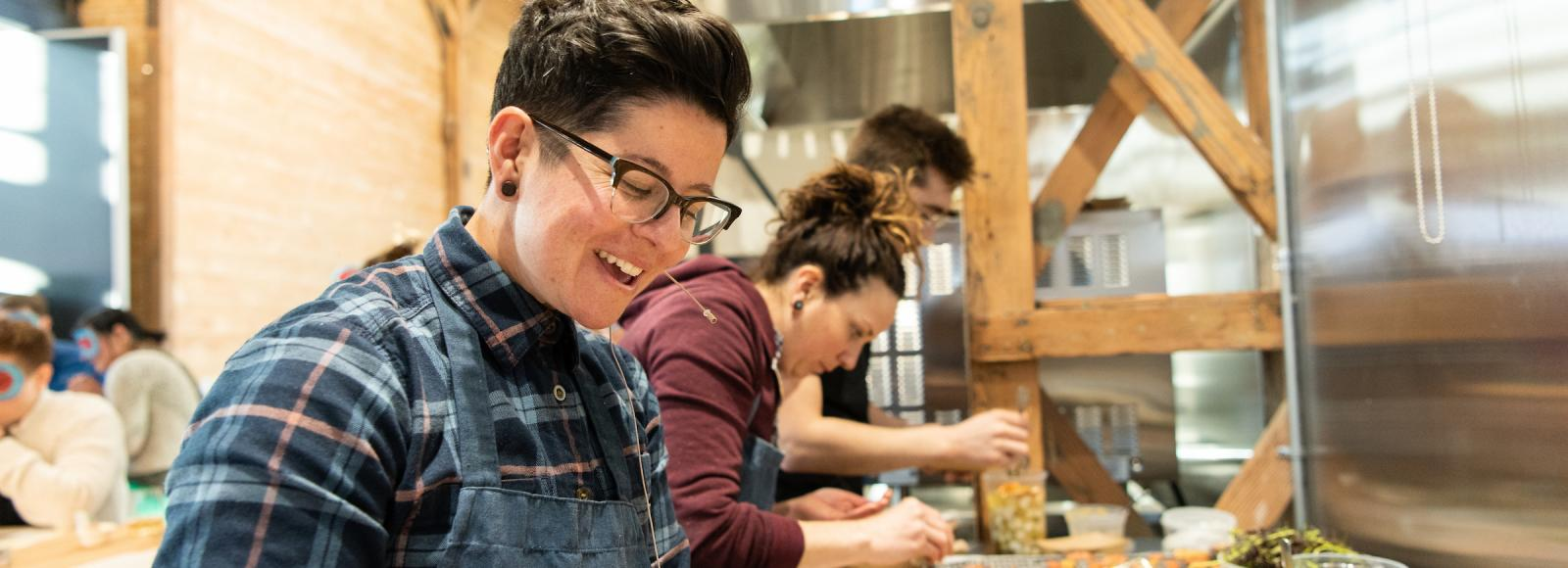A smiling woman in a plaid shirt and blue apron prepares small plates of food.