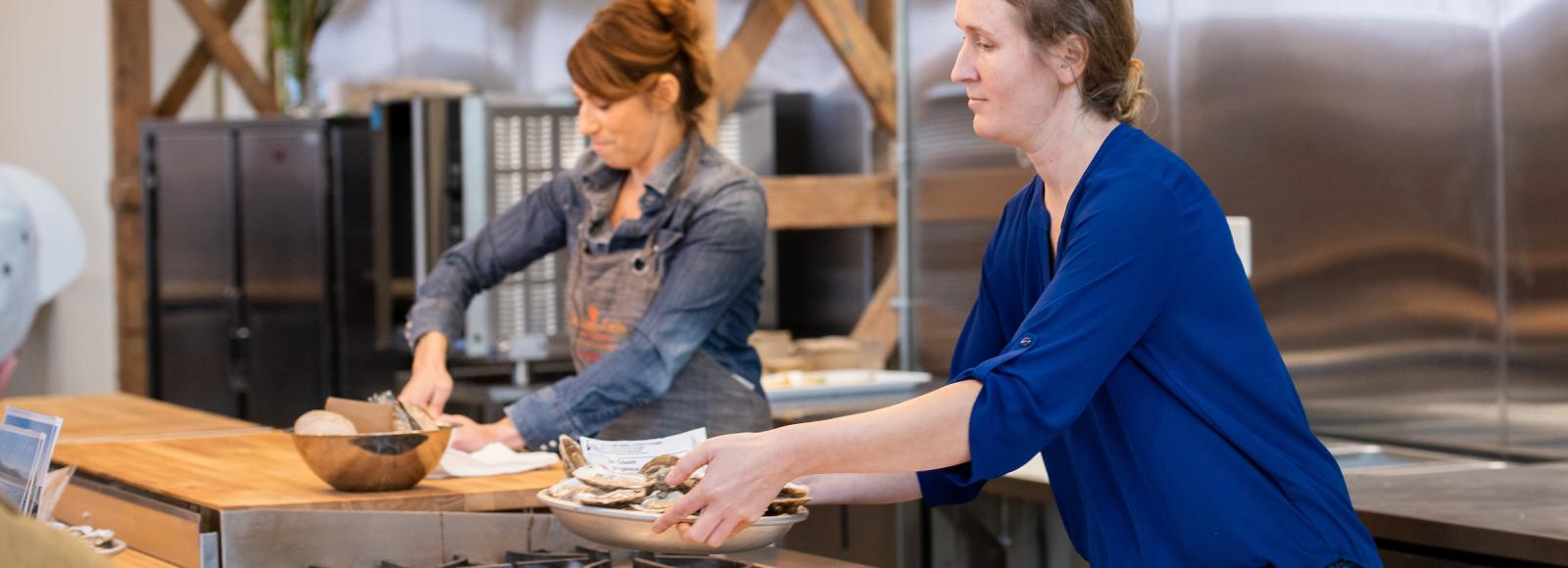 Two women in a large open kitchen share oysters with onlookers.