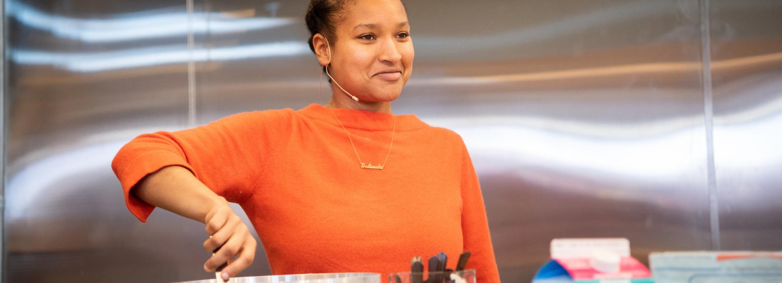 A woman wearing an orange shirt stirs a large silver pot while looking up and smiling.