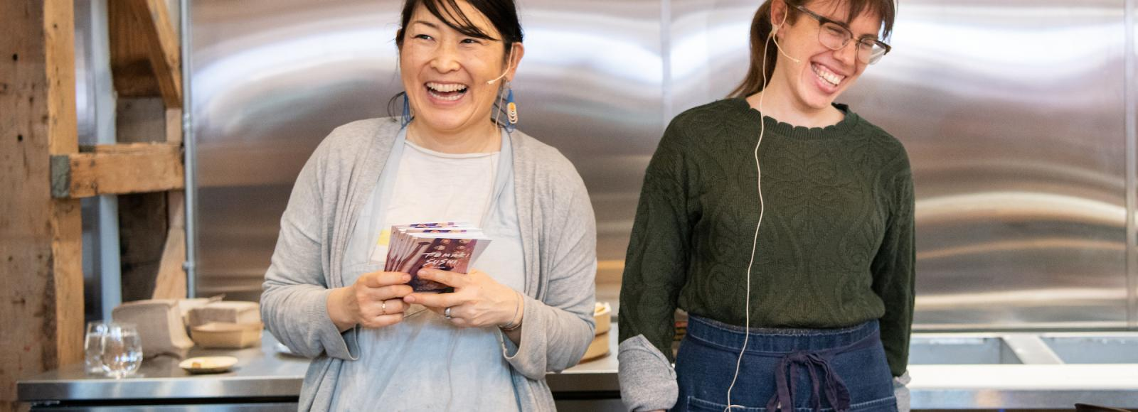 Two smiling women stand behind a large stove in an open demonstration kitchen.