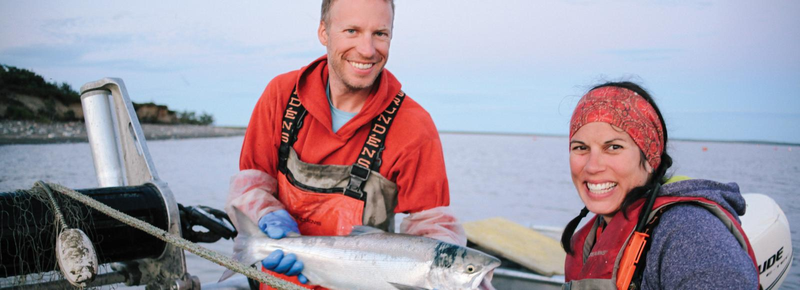 Smiling man and woman in boat wearing orange waterproof overalls, holding a silver salmon
