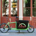 Green bike with black SoupCycle labeled carrier in front of old rust colored double doors