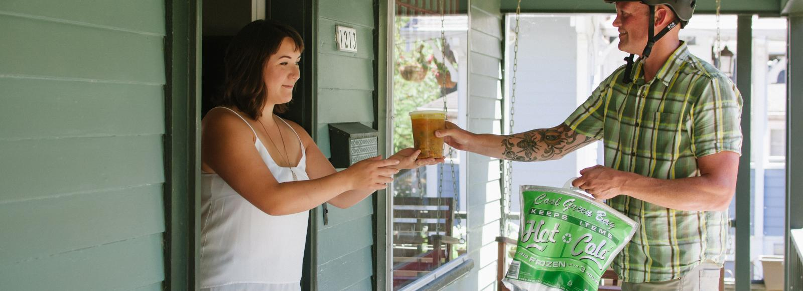 Man in bicycle helmet hands a woman plastic container of soup on covered green front porch