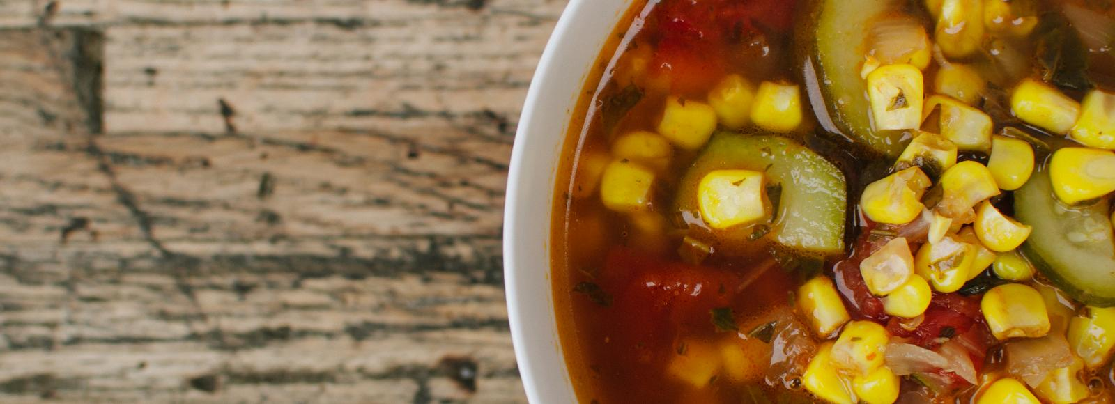 While bowl of vegetable soup with corn, zucchini, and tomatoes on rustic wood table