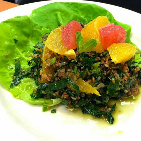 The second place entree: a bright kale salad with citrus supreme and bulgur laid on top of a few bright green leaves of butter lettuce.