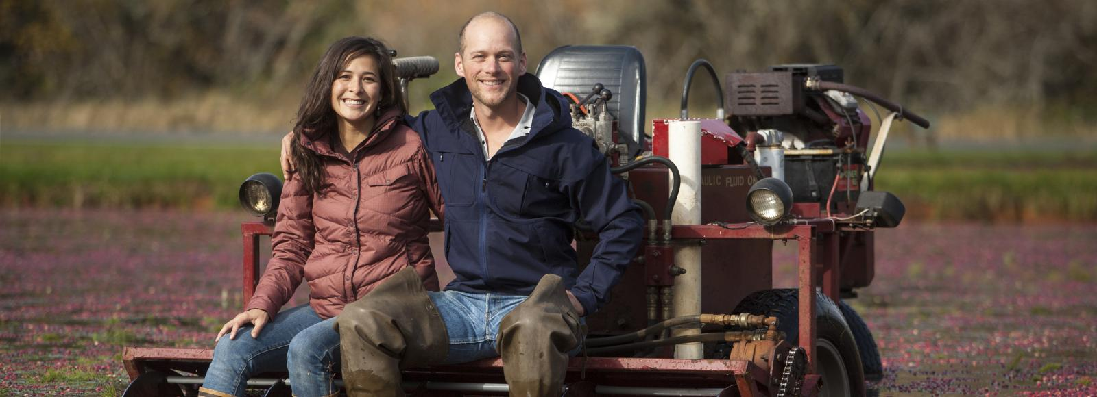 The owners of Starvation Alley, the only certifed organic cranberry farm in Washington, sit on machinery in their bog full of ripe cranberries.