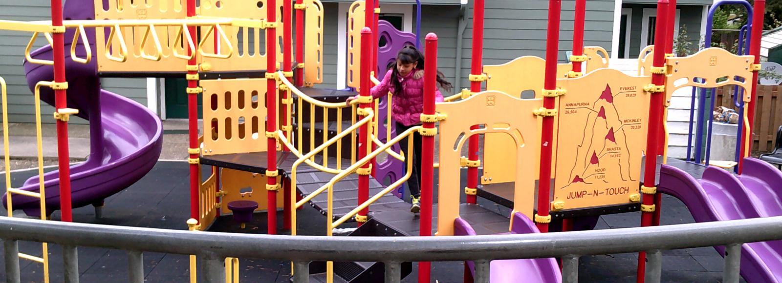 A child on a play structure in the Cully neighborhood
