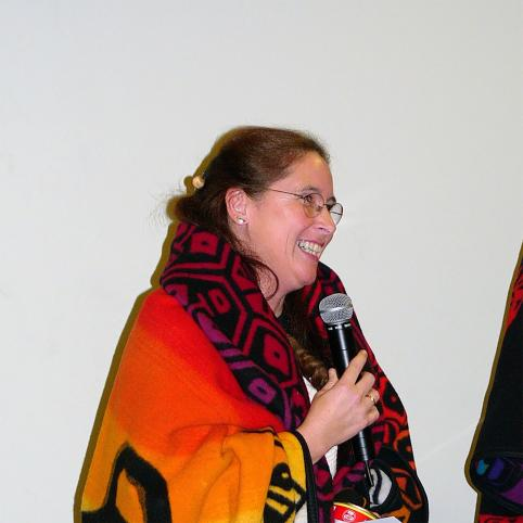 woman holding microphone, wrapped in colorful orange blanket.