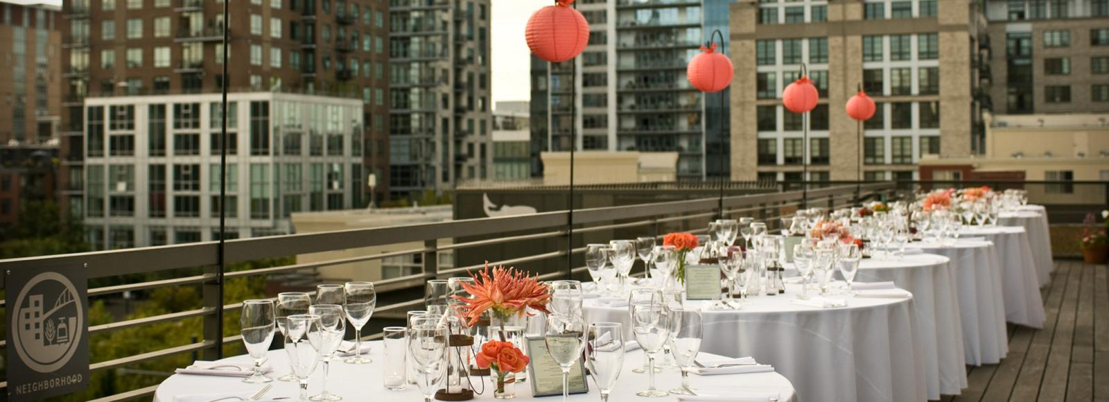 Tables are set for a banquet on the Ecotrust rooftop terrace. White Linens. Wine glasses. Red-orange flowers that match globe paper lanterns. City skyline in the background.