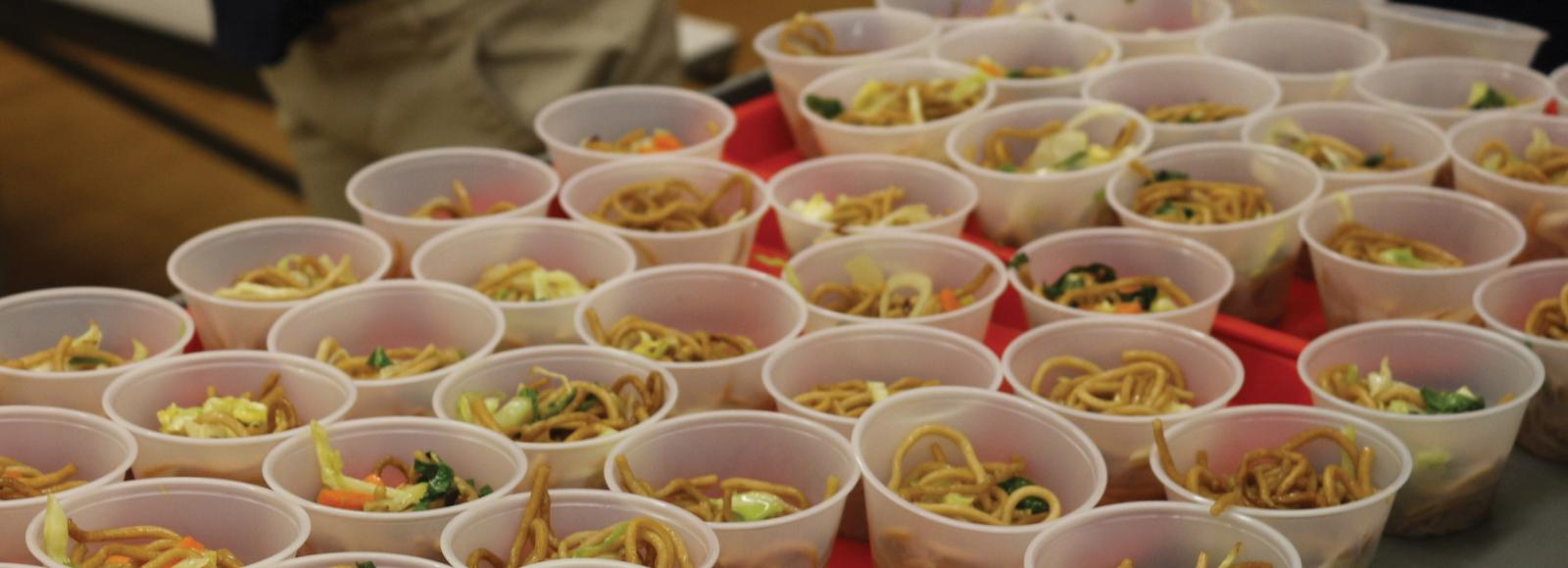 Plastic cups hold samples of noodles, cabbage, and carrots.