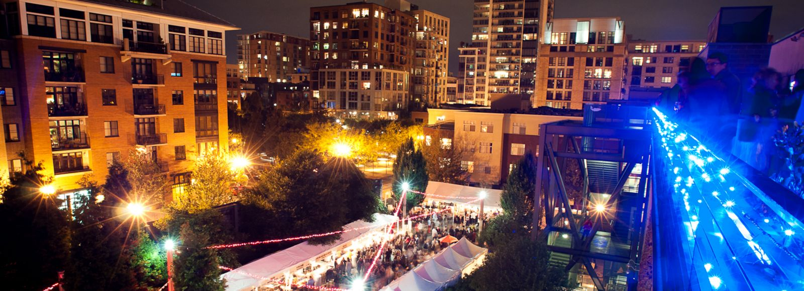 aerial shot of nighttime outdoor celebration with white tents set up, lights strung from above, and crowds of people below rooftop terrace