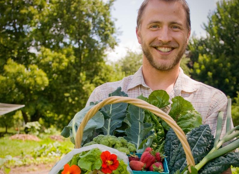 close-up of male farmer smiling broadly while he holds holds a wicker basket overflowing in greens, orange nasturtiums, garlic, and more