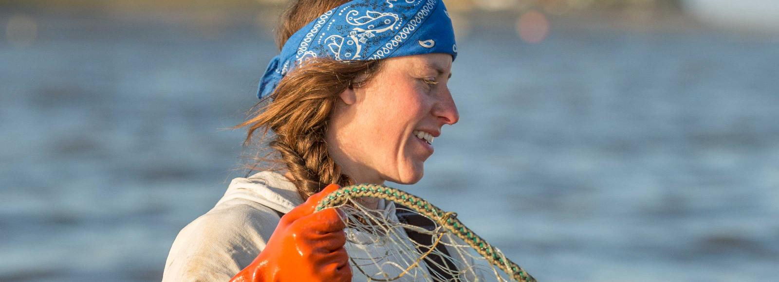 A close-up of a powerful female salmon fisherman pulling in a net.