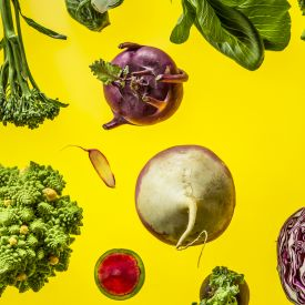 a mix of colorful vegetables on a yellow background: bok choy, watermelon radish, red cabbage, kale, a turnip, brussel sprouts, broccoli