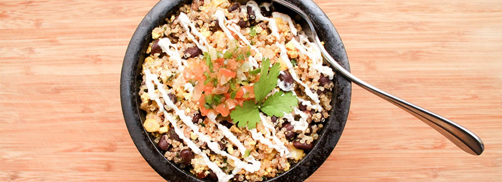 A black bowl with quinoa and other beans and grains.