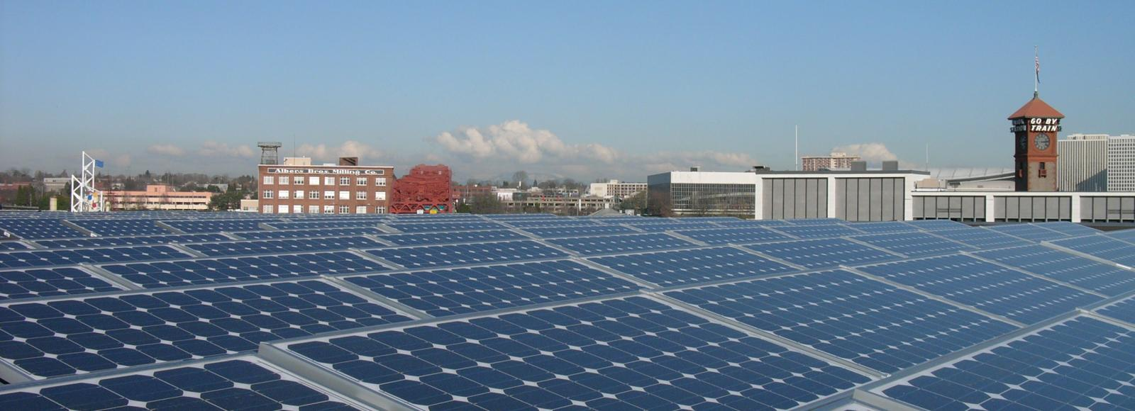 Solar panels on top of the roof of the NCC building in portland. go by train sigh visible.