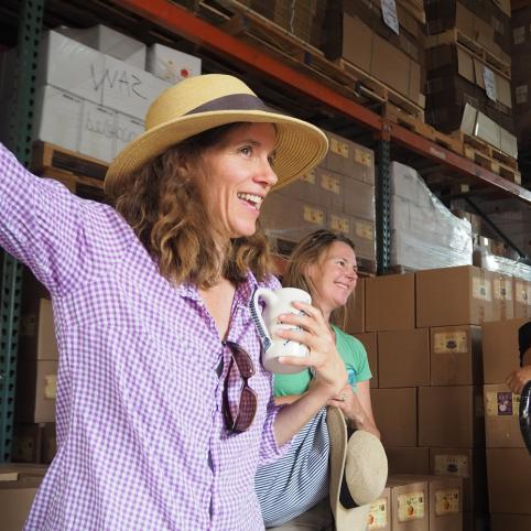 A woman in a straw hat and a purple shirt gestures to a group in front of a wall of stacked boxes.