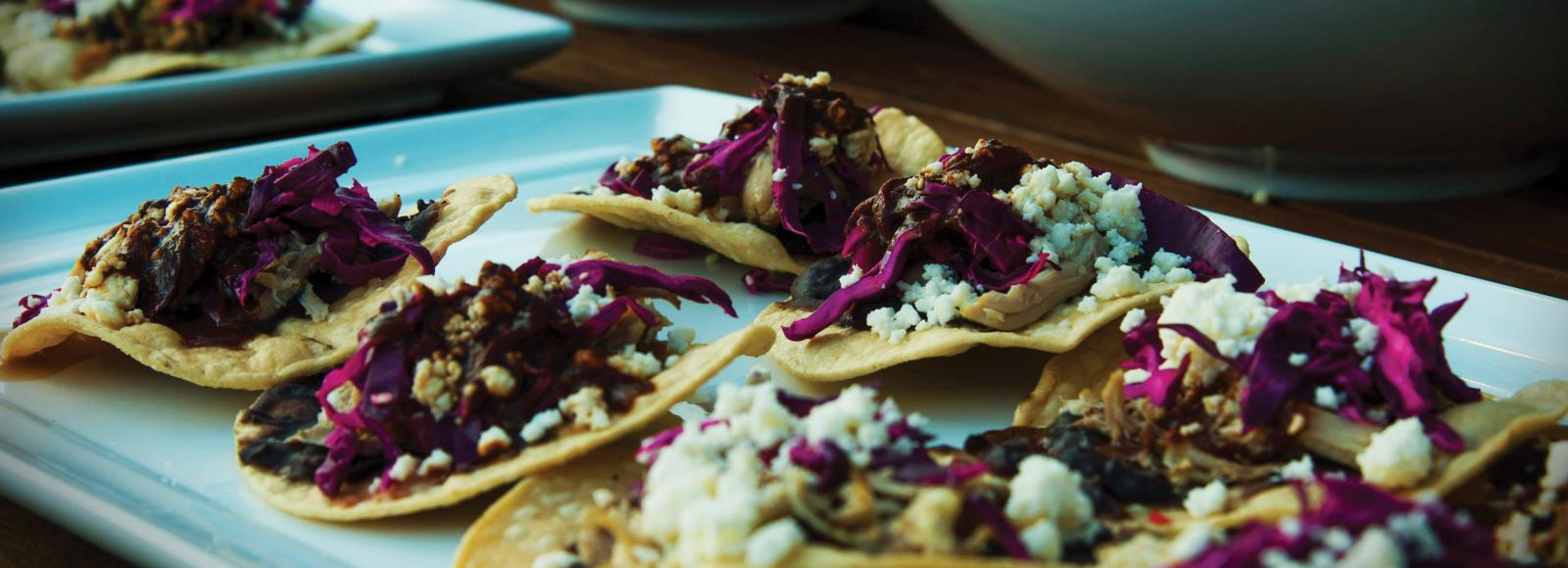 A tray of tacos topped with beef, cabbage, and cotija cheese
