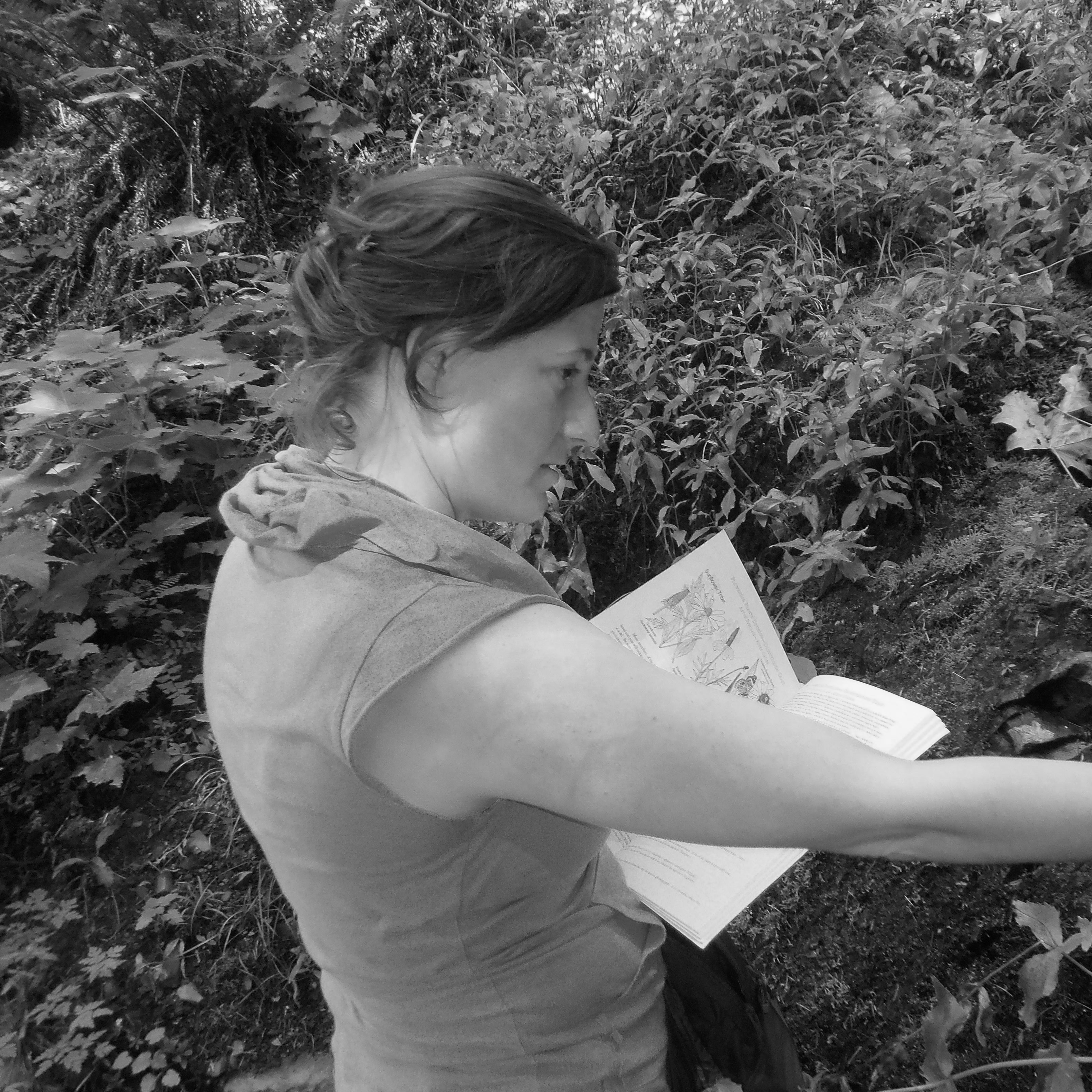 Black and white image of Tiffany Austin reading a book and reaching for a tree