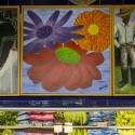 This mural, in North Portland's Village Market, was painted by neighbors and community organizers who collaborated on the plans and vision for a vibrant small-scale grocery store offering healthy foods to an underserved neighborhood. It sits above a vegetable case full of fresh produce. The image shows three flowers in bloom.