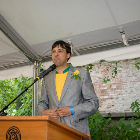 The founder of Nossa Familia Coffee stands on an outdoor stage behind a podium giving an acceptance speech