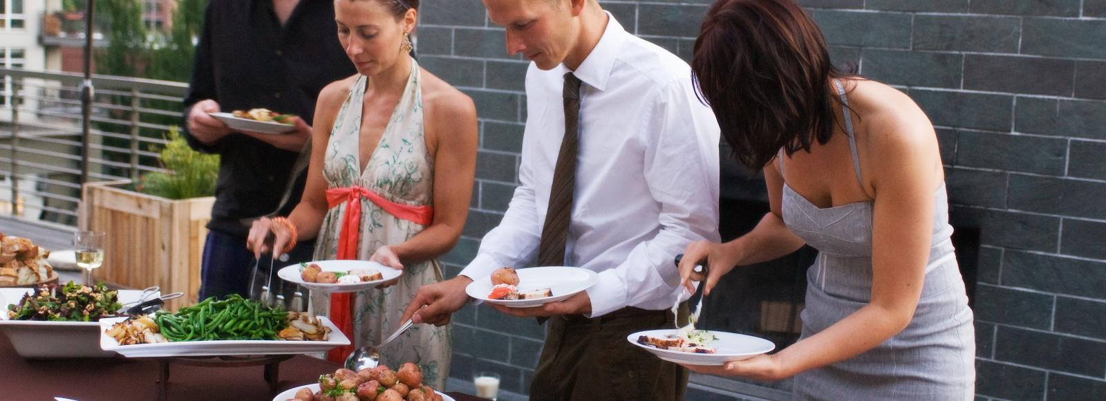 Event goers dish up from a buffet line outside on the Ecotrust terrace