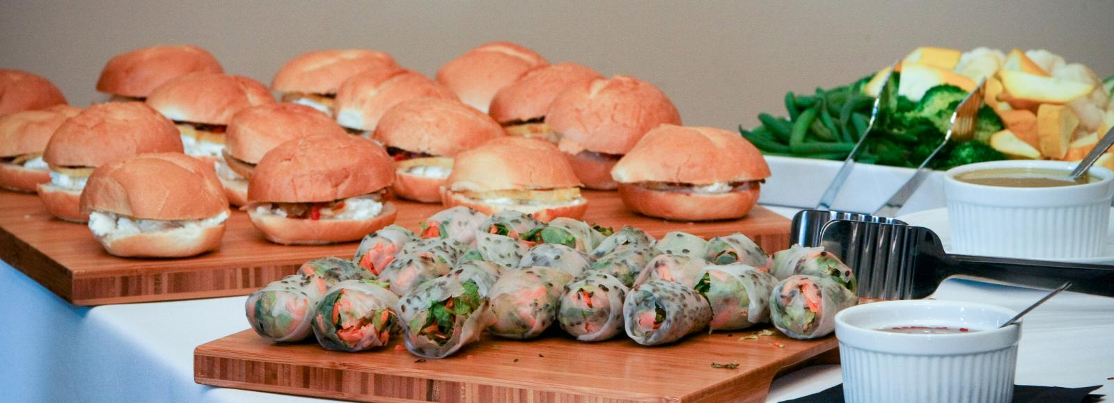 Sandwiches and egg rolls are displayed on bamboo platters