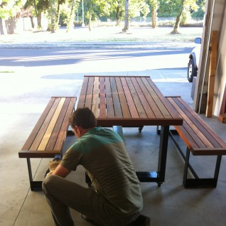 Joel Miller puts the finishing touches on a table built of Viridian salvaged materials.
