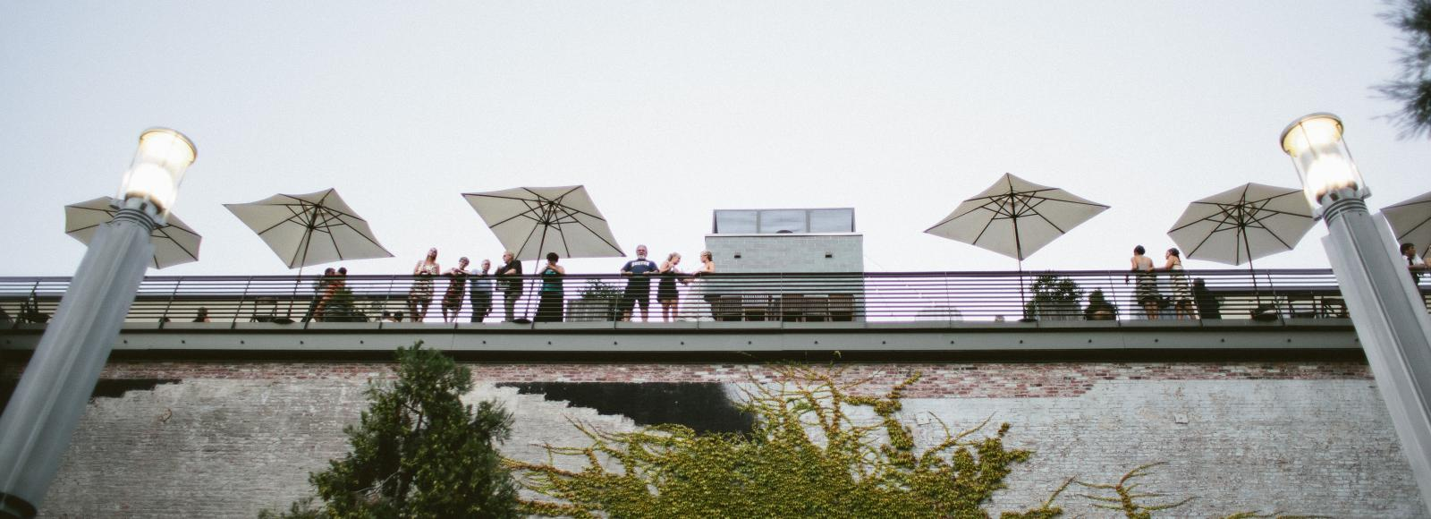 West side of the Ecotrust building, looking up at the terrace from below. Ivy covers much of the brick. The lights are on and the umbrellas are open on the terrace. People are talking and looking down.
