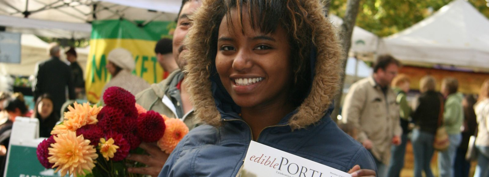 Student displays cover of Edible Portland magazine at farmers market