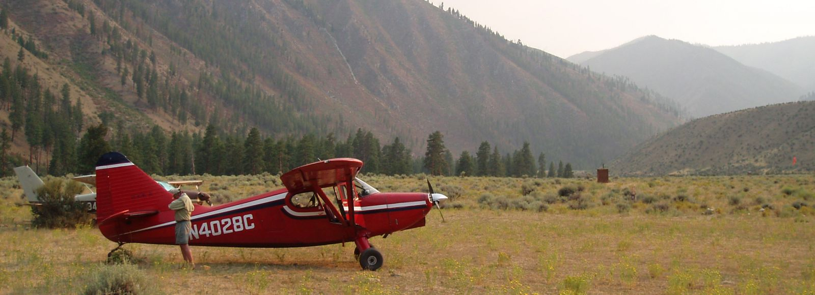 red airplane out in a mountain meadow