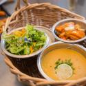 A basket of silver bowls, one filled with salad, one with roasted sweet potatoes and parsnips, one with creamy orange soup; in the background, there is a tray of roasted vegetables.