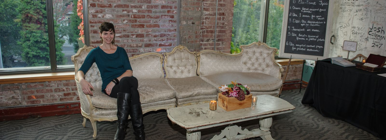Woman sitting on vintage couch, smiling, in front of a brick wall in the Ecotrust building, Portland Oregon