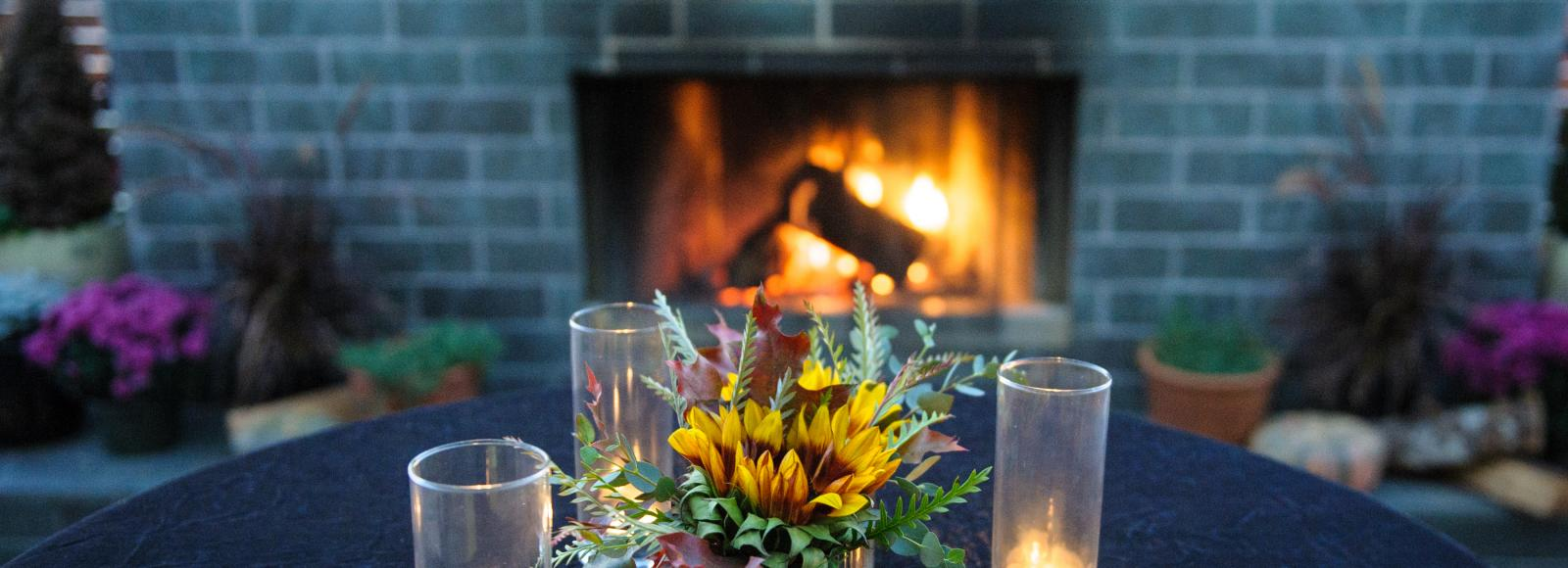 Candles and flowers on terrace in front of a glowing fire