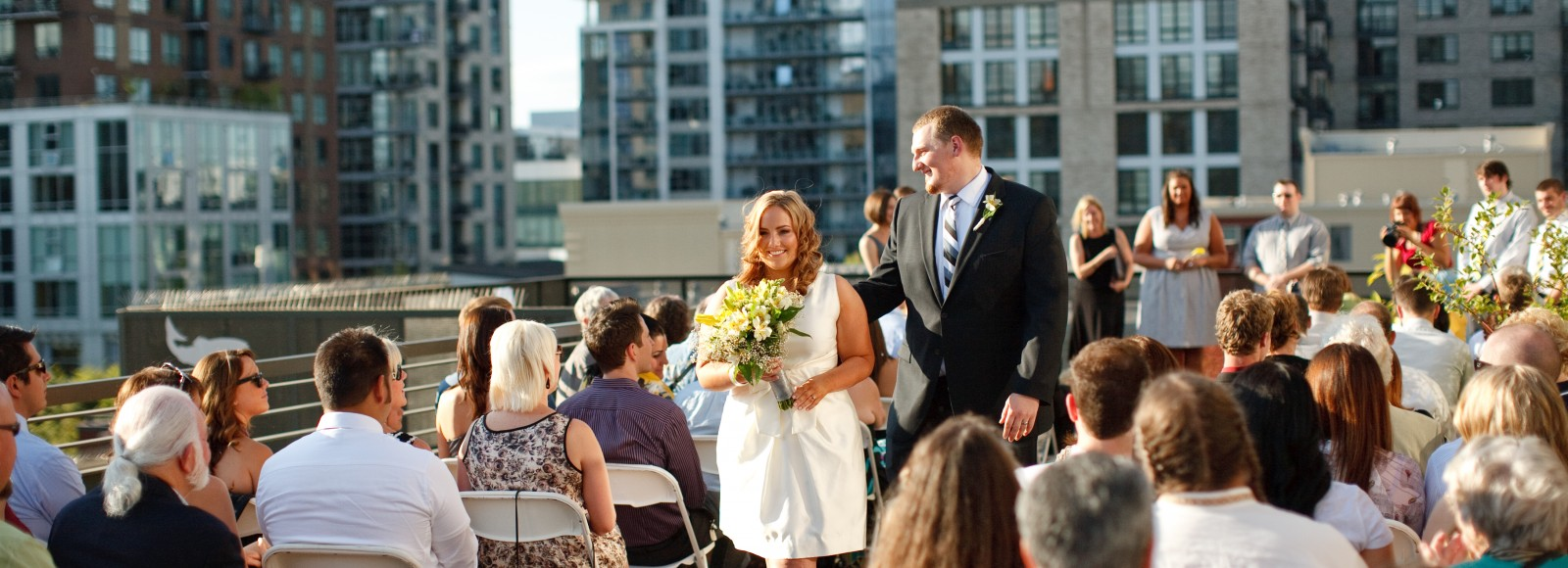 Wedding on the Ecotrust terrace. Bride and groom walk down the aisle. Friends and family on either side.