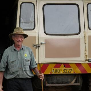 Allan Savory stands at the back of a Land Rover.