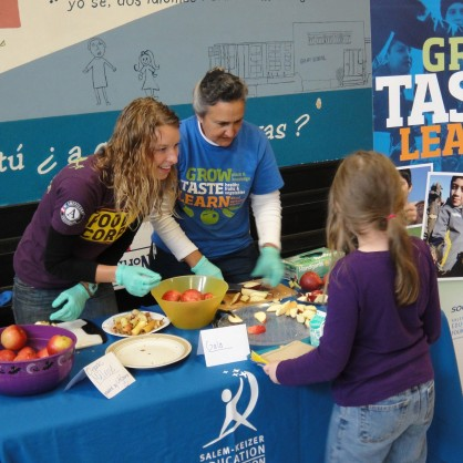 Food Corps Service member Chelsea Thomsen and Salem-Keizer Education Foundation School Garden Coordinator Brenda Knobloch serve tastes of several varieties of Oregon apples to students in the cafeteria at Grant Community School.