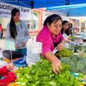 A Latino farmer and her children work a booth at the Forest Grove farmers' market