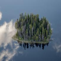 Aerial view of a small wooded island in the midst of still blue water with wisps of clouds. Northern British Columbia.