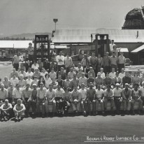 Black and white staff photo from 1977 of the Rough and Ready Lumber Mill Co. Over 100 peope are sitting outside together with the mill in the background. Smiling, sunny, warm.