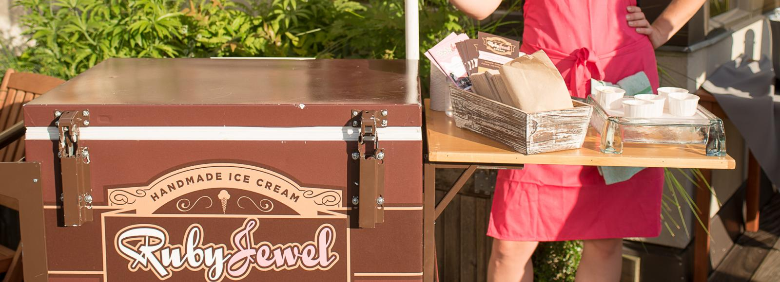 A woman staffs the Ruby Jewel ice cream cart outside under an umbrella