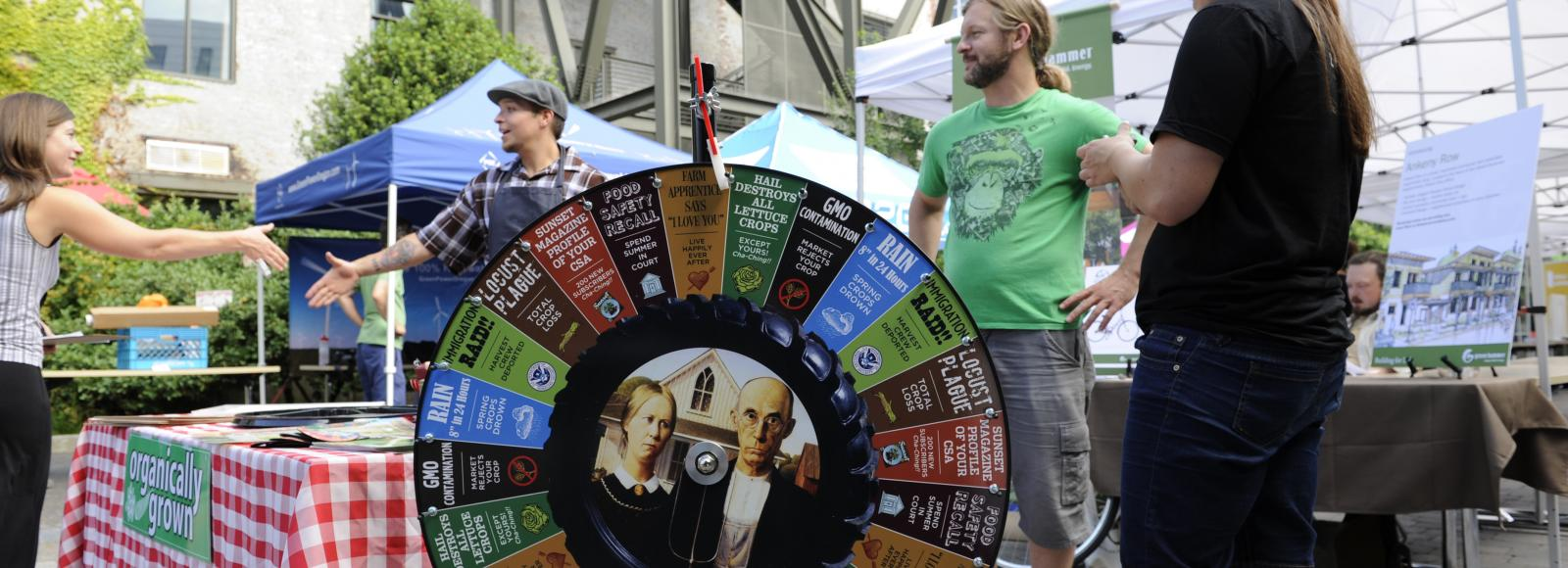 spinning raffle wheel with organically grown booth in the background