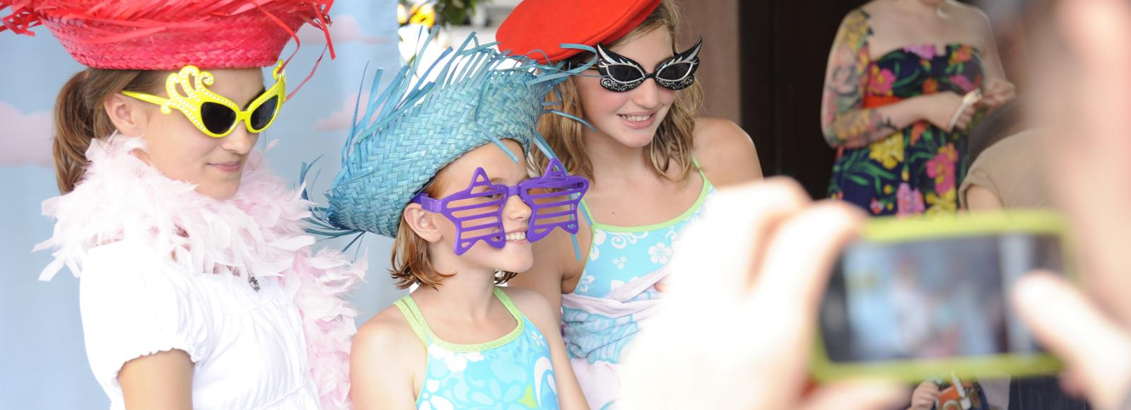 Three girls dressed up with hats and sunglasses