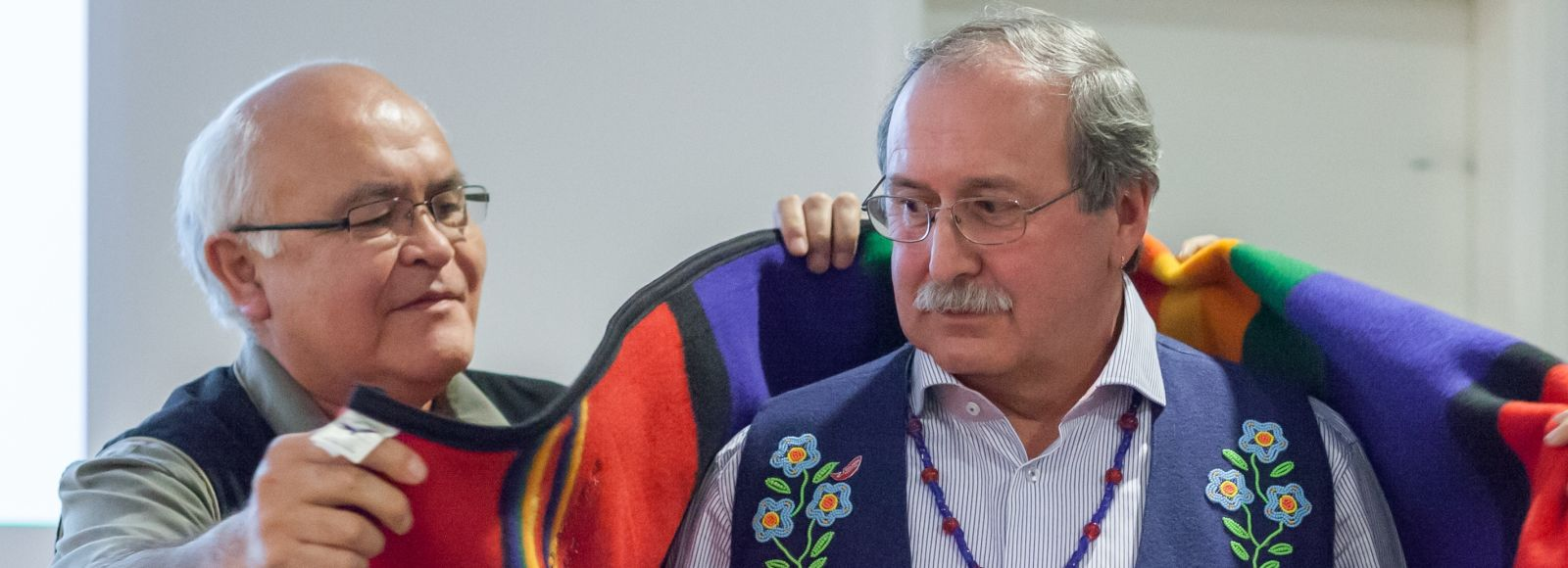 A blanket is draped on the shoulders of indigenous leader Art Sterritt