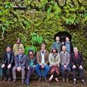 A group of people pose in front of a mossy wall on a rainy day